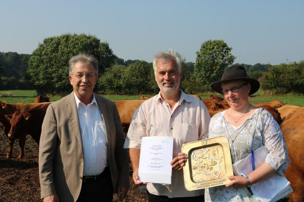 For successful breeding: Claus Heller, president of the chamber of agriculture (left), presents the award to Mr. and Mrs. Clausen in Mittelangeln (Satrup). Picture: LK- SH