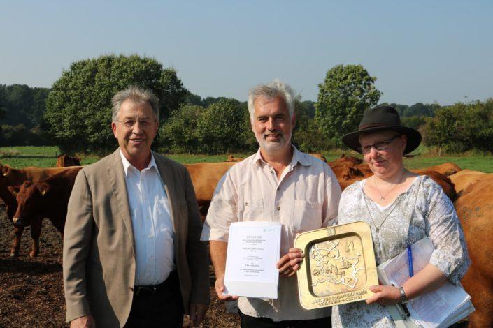 Für erfolgreiche Tierzucht: Landwirtschaftskammerpräsident Claus Heller (l.) übergibt die Auszeichnung an das Ehepaar Clausen in Mittelangeln (Satrup). Foto: LK- SH